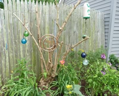 A brass sprinkler adds to the eclectic mix in this summertime garden along the Green Thumb garden tour.  #garden
