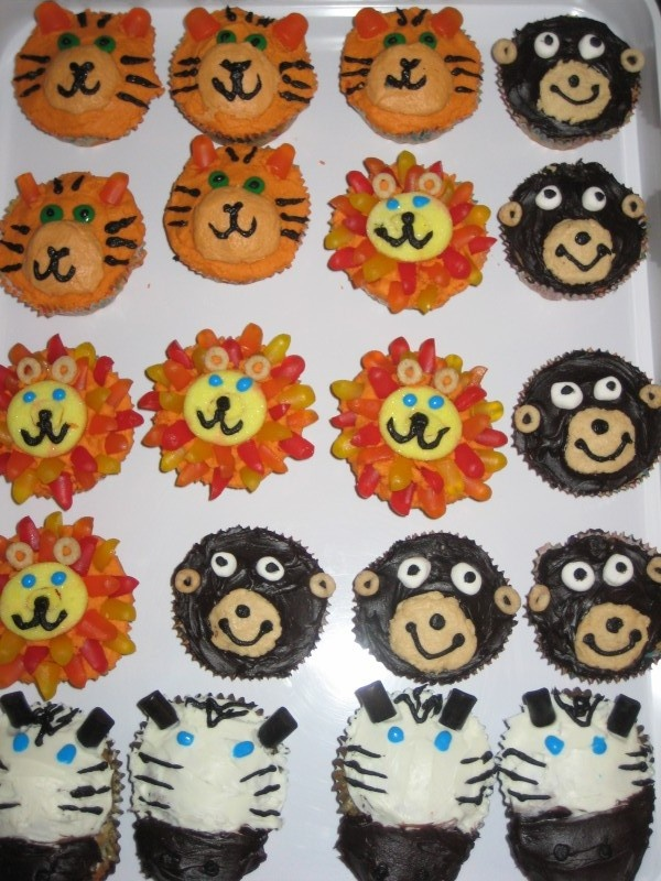 """I made these for my son's 3rd birthday party (jungle theme). I use 2 shades of orange frosting for the tiger. Lions were made with a candy peach ring & a smaller piece cut out to fill in the center, his ears are cheerios & his mane is made of Dots candies cut into pieces & """"glued"""" on with orange frosting. The zebra's nose is made by making a slit in the front of cupcake and pushing a round nutter butter (Target brand) in the slit, then frosting with black frosting. Milano cookies will also…"""