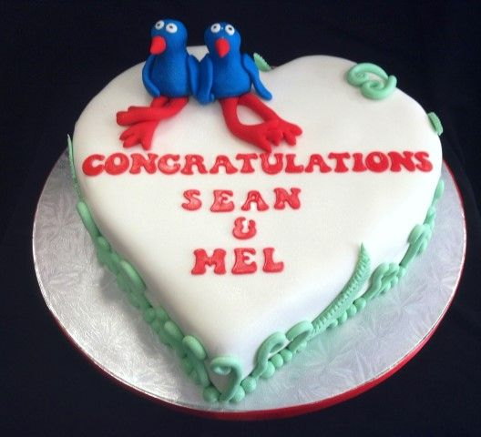 Kiwi inspired pukeko engagement cake. This cake has a custom topper of 2 pukeko's holding hand sat on top of a heart shaped cake with ferns and korus wrapped around the edge.