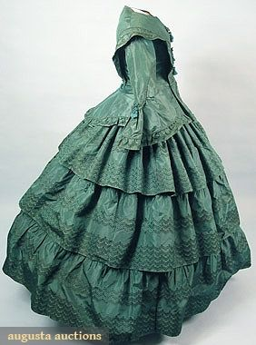 "American Green Silk Day Dress (1855-1860). 2-piece taffeta woven en disposition, fitted bodice w/ peplum & large pagoda sleeve, skirt w/ 3 tiers, knotted & fringed frogs, attached paper tag ""Aunt Sallie Hendrickson's green silk dress Woluford Original"", Sh-Sh 17"", B 37"", W 24"", Skirt L 42"","