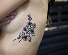 Beautiful blackwork florals on rib cage by Kristi Walls