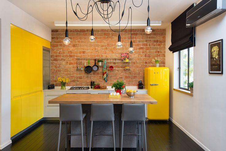 ארונות המטבח תוכננו בצורת האות ר': על קיר הלבנים האדמדמות פס של ארונות לבנים נמוכים, ולצידו ארונות גבוהים בצהוב, כצבע המקרר ( צילום: אביב קורט )