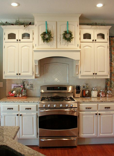 tiny boxwood wreaths above the stove (Chris Carleton at Pink Picket Fence) (love her stuff!)