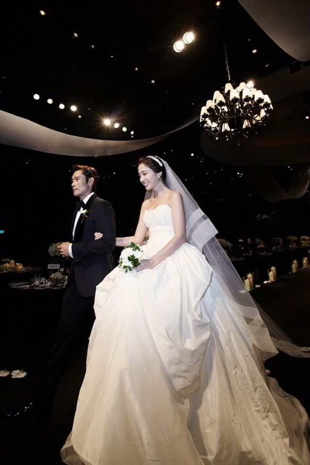 Korean stars Lee Min Jung and Lee Byung Hun who starred in GI Joe and Red2 celebrated their wedding this week. The couple got married at the Grand Hyatt in Seoul, Korea. Lee Min wore 3 different dresses, she first wore a simple dress with lace sleeves by Marchesa 2013.