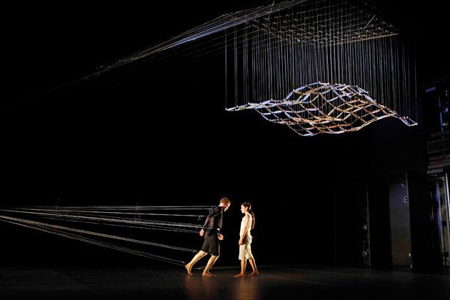 """String in dance piece """"Connected"""" using big contraption that attaches dancer to sculpture"""