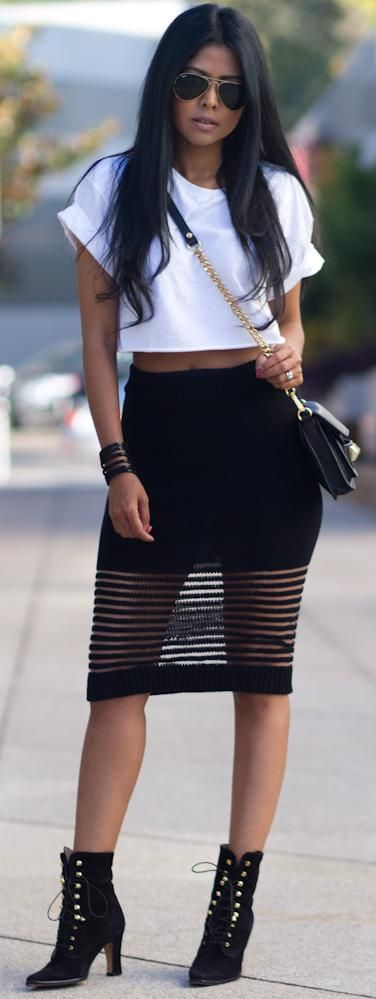 Long black skirt with see through bottom stripes , boots and half wh shirt .