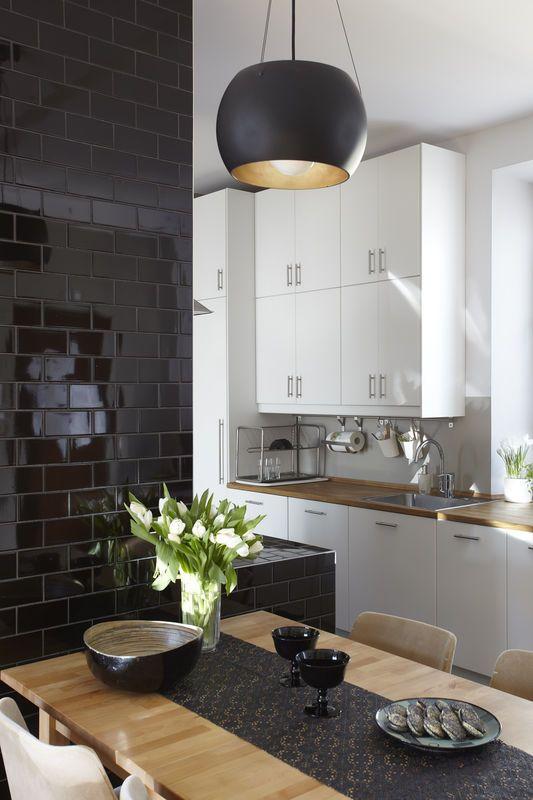 Proste białe meble w połączeniu ze ścianą obłożoną czarnymi kaflami tworzą klasyczny duet kolorystyczny w tej otwartej kuchni. Lampa nad stołem i dekoracyjne dodatki w czarnym kolorze sprawiają, że wystrój jadalni jest spójny z aneksem. A drewniane blaty kuchenne i stół go wizualnie ocieplają.