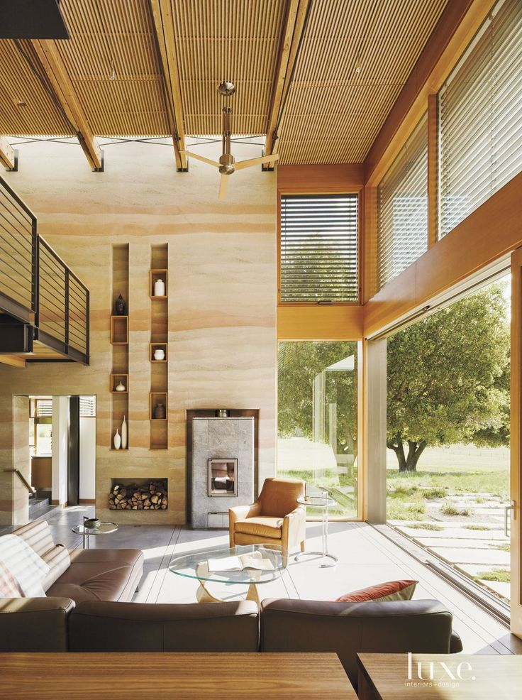 A house south of the bay area, designed by architect Jonathan Feldman, features rammed-earth walls that play off expanses of glass and reclaimed-wood accents. The owners furnished the living room with a leather Roche Bobois sectional and a classic Isamu Noguchi coffee table.