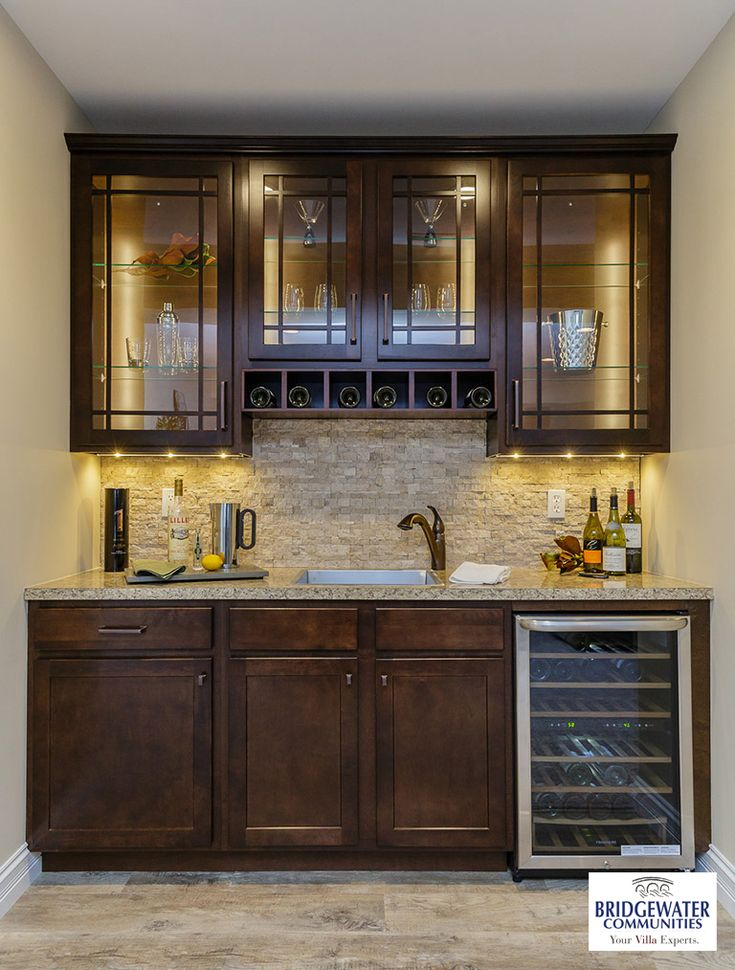 Bridgewater's custom bar in the finished lower level. Includes glass front cabinets with LED cabinet and under cabinet lighting, a beautiful stacked stone backsplash, an oversize zero radius stainless steel sink with pull out faucet, custom cabinetry and a wine refrigeration cabinet.  http://www.bridgewatercommunities.com