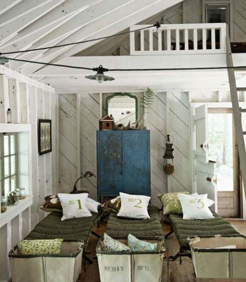 Une rangée de lits en bois ancien et paniers cru remplir la cabine des enfants, avec beaucoup de possibilités et d'espace pour accueillir des soirées pyjama pour les amis.  Toile oreillers numéro impression ont été faits à la main par Kim Reding.