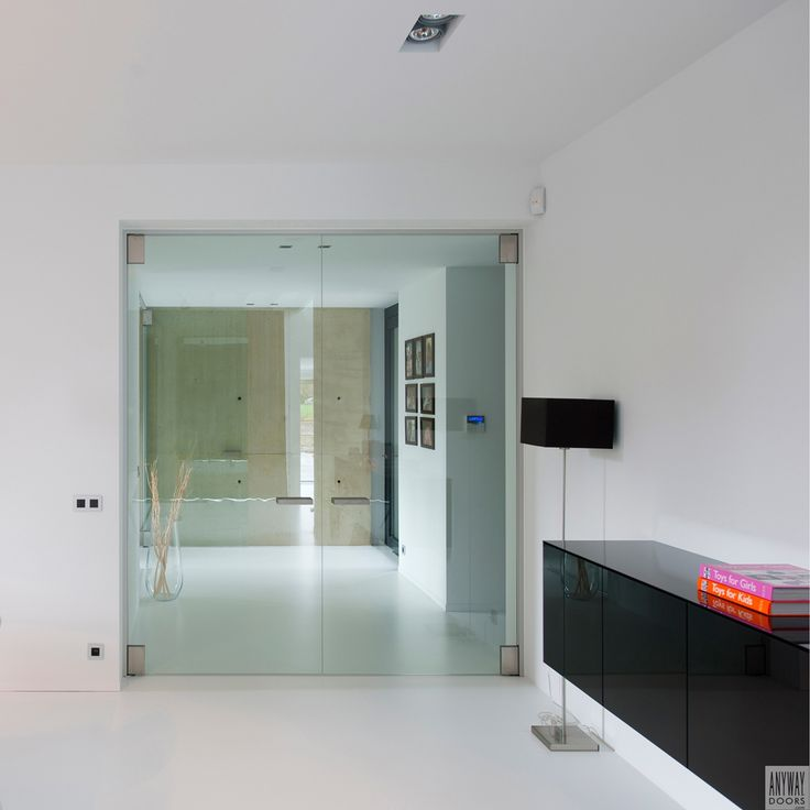 Modern double glass doors between entrance and living area. Custom-made by Anyway Doors, without any floor fixtures.