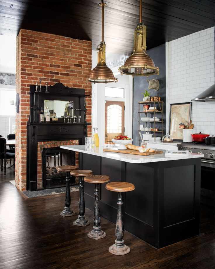 An industrial kitchen with black painted ceiling, exposed brick fireplace, wood kitchen stools, and large pendant lights