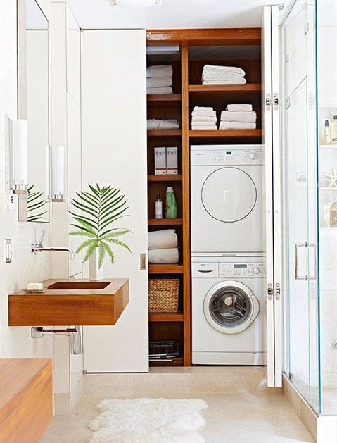 21 Laundry Rooms That Will Make You Want to Do Laundry - appliances tucked into the closet of a spa-like bathroom