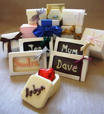 Could use these as place names and as favours killing two birds with one stone. Could buy chocolate slab moulds from Lakeland and buy ready made icing and get someone with a steady hand to pipe names on. Could put them in cellophane bags (also from lakeland) and tie with purple ribbon instead of buying boxes