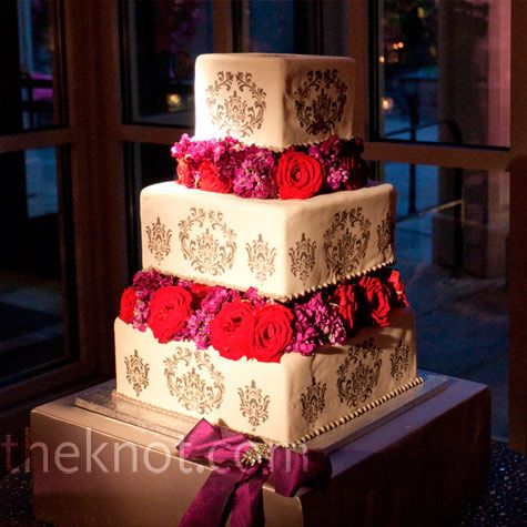 Each of the cake's three tiers was separated by big red and magenta roses and hydrangeas. The stenciling on the fondant resembled the couple's invitations.