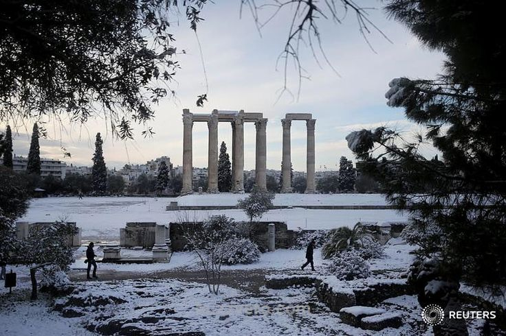 Visitors make their way inside the archaeological site of the ancient Temple of Zeus following a snowfall in Athens, Greece, January 10, 2017. buzzvero Konstantinidis @alkisk_ buzzvero buzzvero #greece #snow #athens #winter #weather #news #gossip #world #funny #crazy #omg #celebrity #