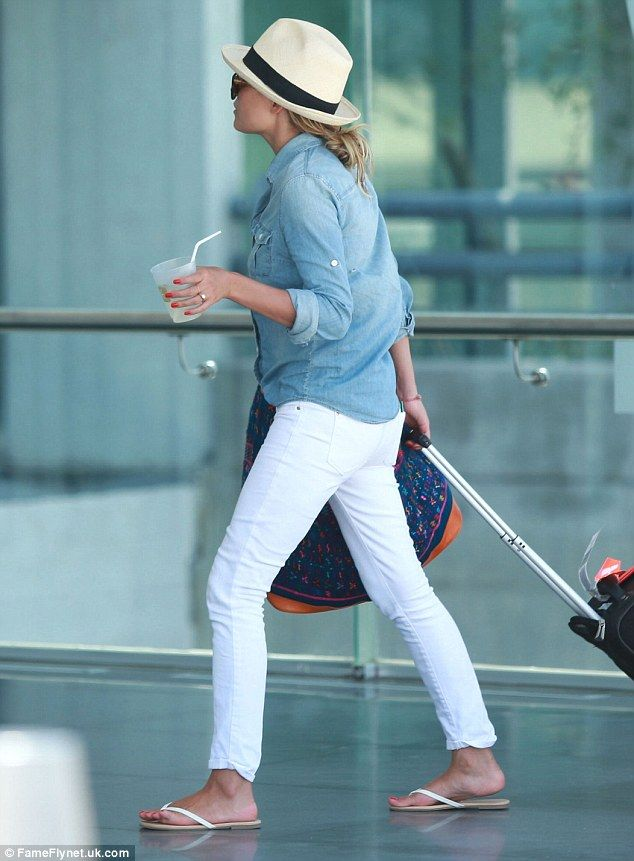 Travel chic: Lauren  Conrad  stylish in white jeans, a denim shirt, and white flip flops, topped off with her trust fedora and sunglasses.