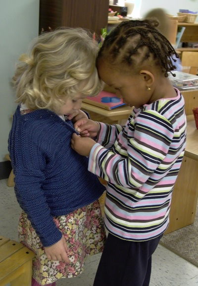 Students helping each other at a montessori school ...