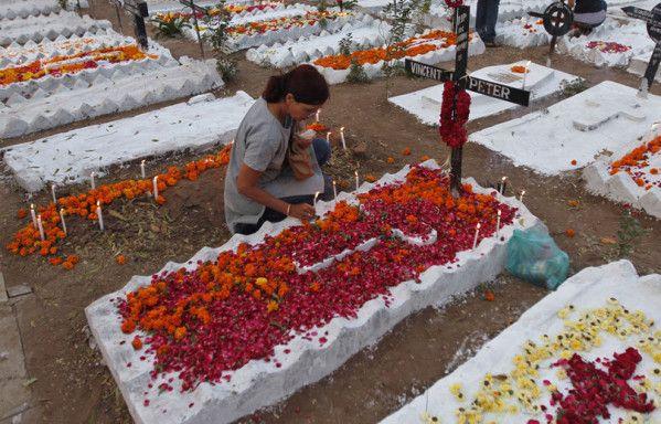Une femme chrétienne dispose des bougies sur la tombe d'un membre de sa famille, au cimetière de Ahmedabad (Inde).