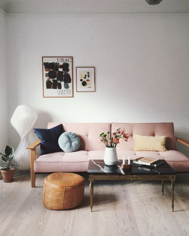 Living room with pale pink sofa bed in an Artful A…