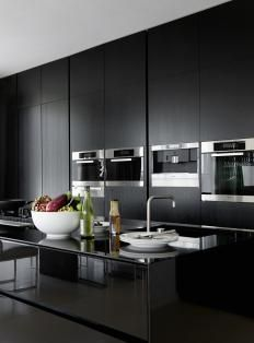 stunning sleek modern kitchen with sophisticated contrasts of dark wood finishes and stainless steel