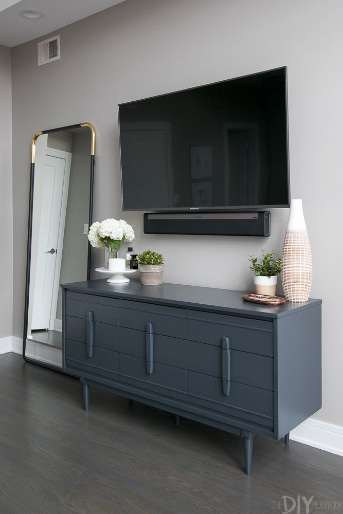 Love this gray bedroom dresser with the TV mounted above it. Plus then you can use the top of it to display pretty accessories. Love the large vase and wood tray from HomeGoods. Don't forget to add some height to the dresser with a cake stand! You can then display perfume and candles on top. (Sponsored Pin).