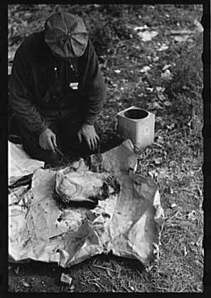 Man in hobo jungle killing turtle to make soup, Minneapolis, Minnesota. Sept. 1939. Photographer: John Vachon.