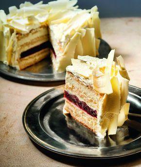 Μια εντυπωσιακή λευκή τούρτα που στο εσωτερικό της κρύβει μια απολαυστική στρώση από ζελέ βύσσινο.