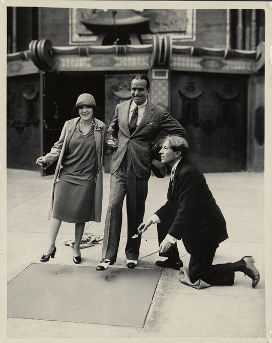 Did you know: Mary Pickford and Douglas Fairbanks, two of the founding members of the Academy, were the first two actors to have their footprints and handprints immortalized in cement outside Grauman's Chinese Theater in Hollywood? Here the couple are with Sid Grauman on April 30, 1927.