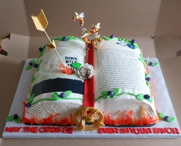 """Hunger Games cake. Mockingjay pin, arrow with flames, Tracker Jackers, Nightlock berries. """"May the odds be ever in your favor!"""""""