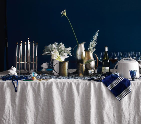 """""""I like a relaxed Hanukkah table in traditional colors. A cluster of pitchers makes an informal centerpiece that you can leave in place and refresh all season. With a menorah—or even without one the effect is sculptural, almost like a skyline."""" —Jeffrey W. Miller, Stylist"""