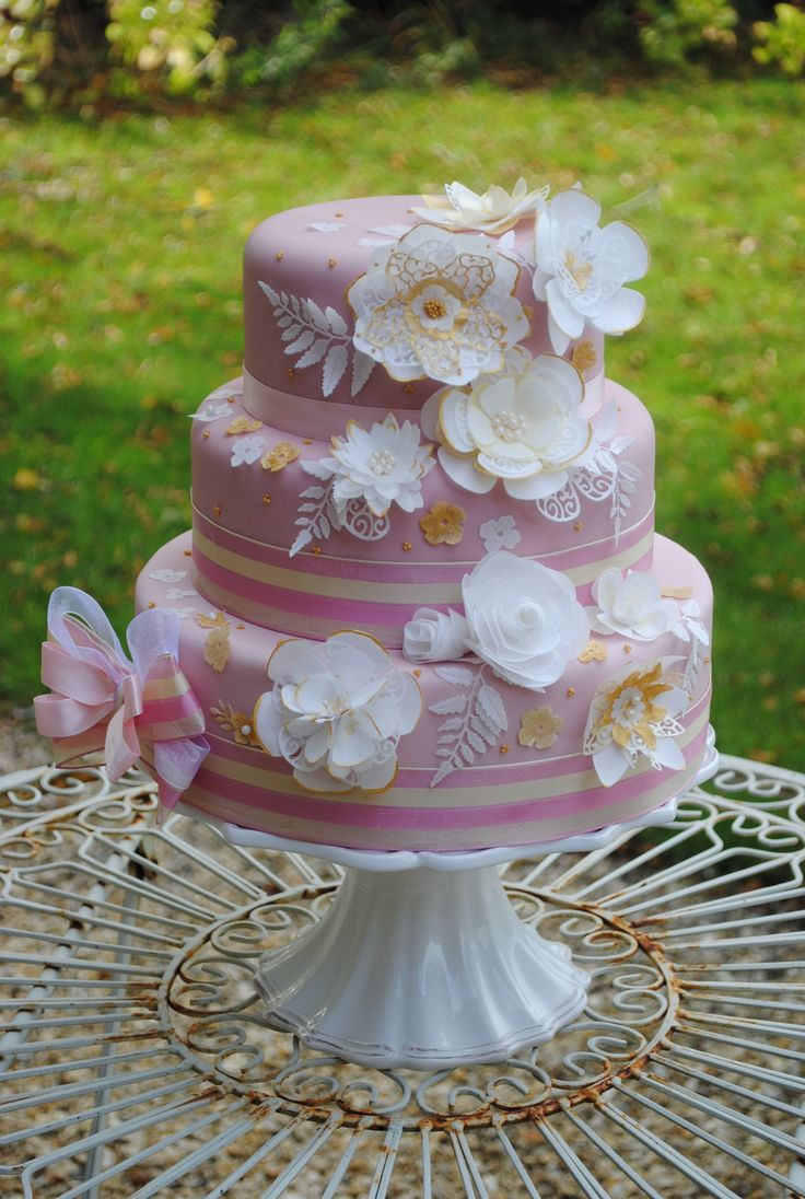 We decided to add a third tier to this cake and continue the cascade of assorted flowers to the larger bottom tier. Cake Crafting's cake dies have been used to cut poppies, roses, lilies and asters alongside smaller blooms and leaves. The side of the cake has been decorated with a large bow using our Bow Maker. Visit www.cakecrafting.co.uk.