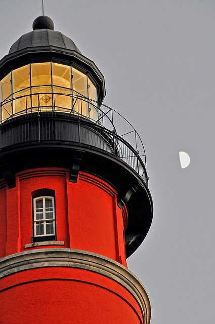 The deep red surrounded by the charcoal black ringed balconies and the yellow light guiding its ships in safely this Lighthouse is a magnificent piece sitting on the shore.