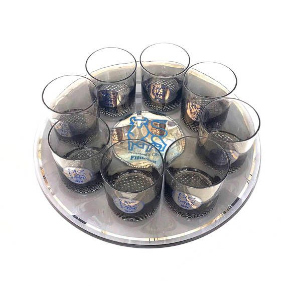 Glass barware set with a large round glass serving tray and 8 matching rocks cocktail glasses. With the Merrill Lynch logo, the set commemorates the 5th Anniversary of the Merrill Lynch Presidents Club. Dated 1976 Smoky glass with silver and blue accents. The cocktail glasses have a pebbly bottom. 13 inches - tray diameter Glasses - 3 inches tall 2ith a 2 3/4 in diameter. Excellent condition. No chips or cracks and very minimal silver loss.  Please see SHOP POLICIES for more info on vint...