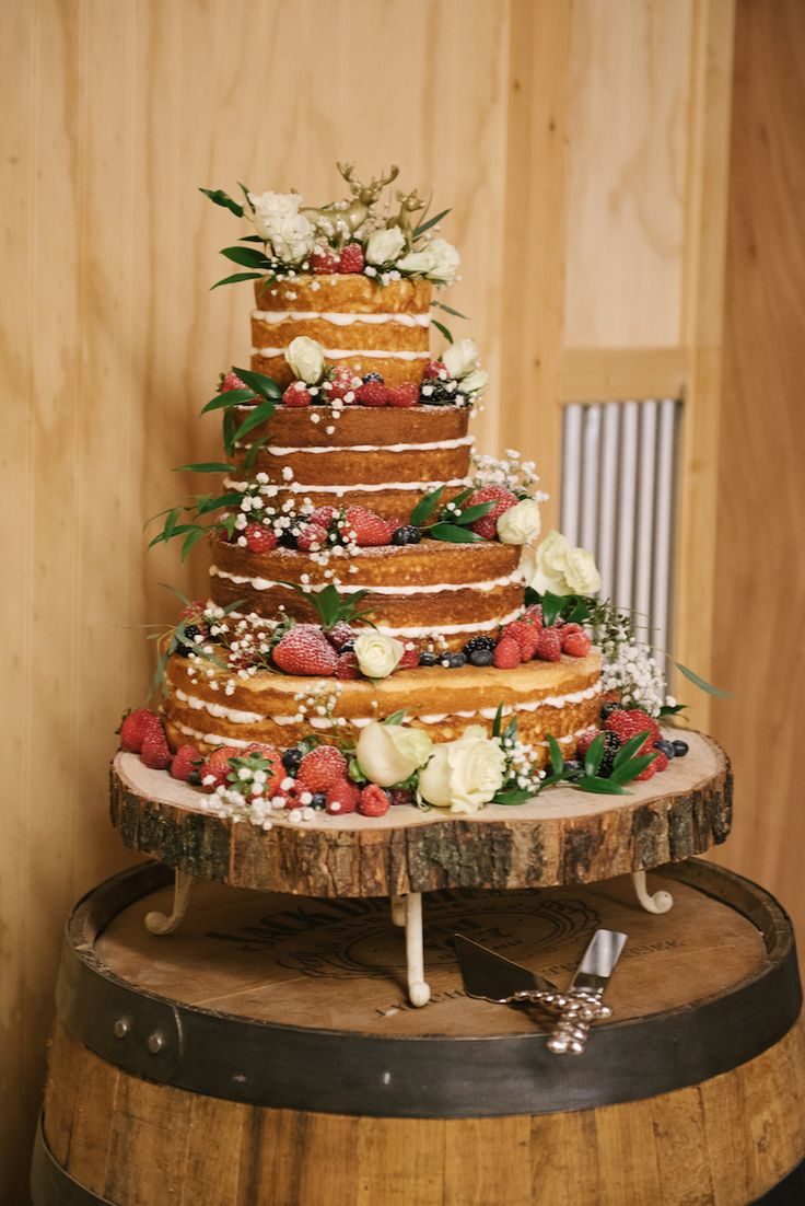 This multi-tiered naked cake covered in fresh berries and blooms went perfectly with Taylor and Joshua's woodland wedding.
