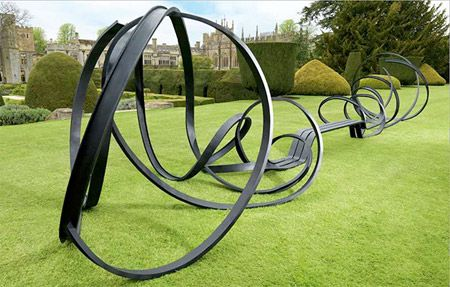 Bent lines  Beautiful park bench designed by Pablo Reinoso from Argentina. This is a more than 9 meter long bench made from steel. the bench is a continuous form comprised of  three steel bars which from one end start as an abstract swirling form flowing smoothly into the actual 'seat' of the bench. - See more at: http://www.archieli.com/design/10-creative-benches/#sthash.gNK2Ao8v.dpuf