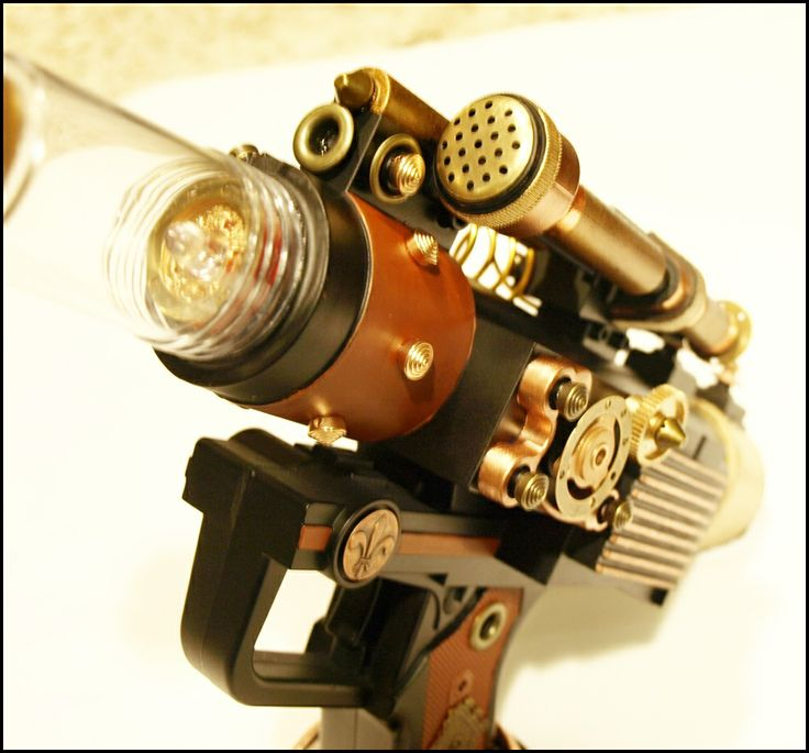 Custom modded gun i created as a Steampunk Gun. Custom painted in Satin Black. Hand painted in gold, brass, copper and rust colors by Testors paints. I detailed the areas with custom parts, gears, aluminum wiring, Plastic  cast aluminum parts for more detailed realism. Comes with a working integrated red LED light and sound blaster sounds. A real nice piece to add to any collection.