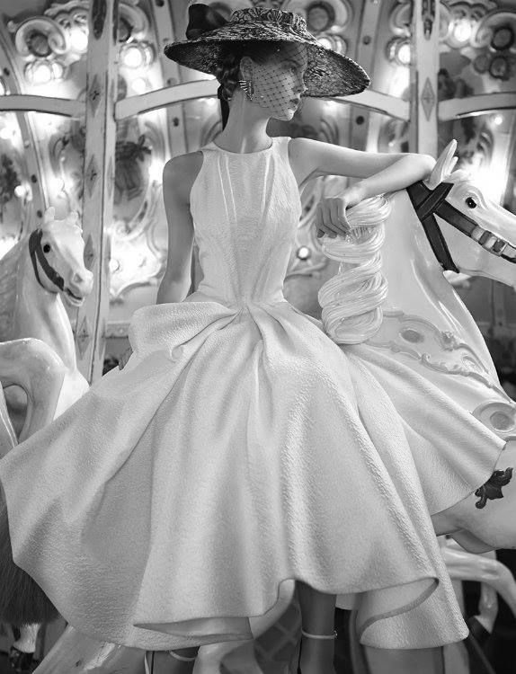 Anne Gunning on a carousel wearing a white pique' fit & flare dress with a camisole bodice. Photo by Norman Parkinson.
