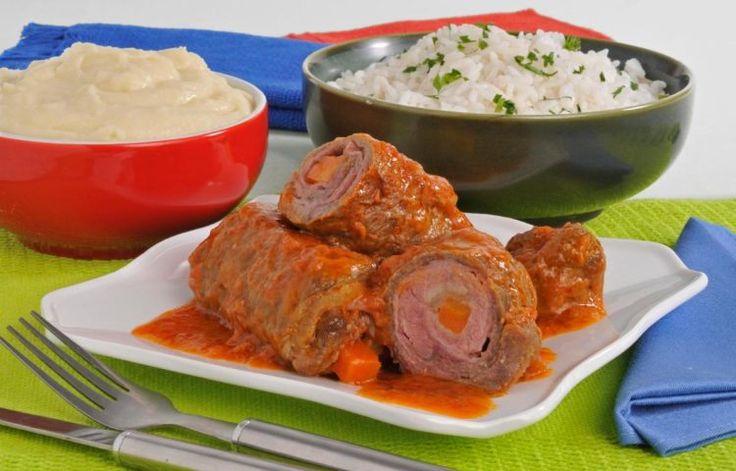Foto com a receita do bife rolê com molho italiano, disposto em um prato branco, com bastante molho. Ao fundo, a receita está acompanhada de uma tigela de arroz e outra com purê de batata.