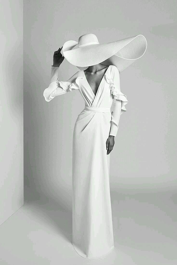 elegantes Porträt einer Frau, die einen enormen weißen Sommerhut und ein lange… – Langes Kleid