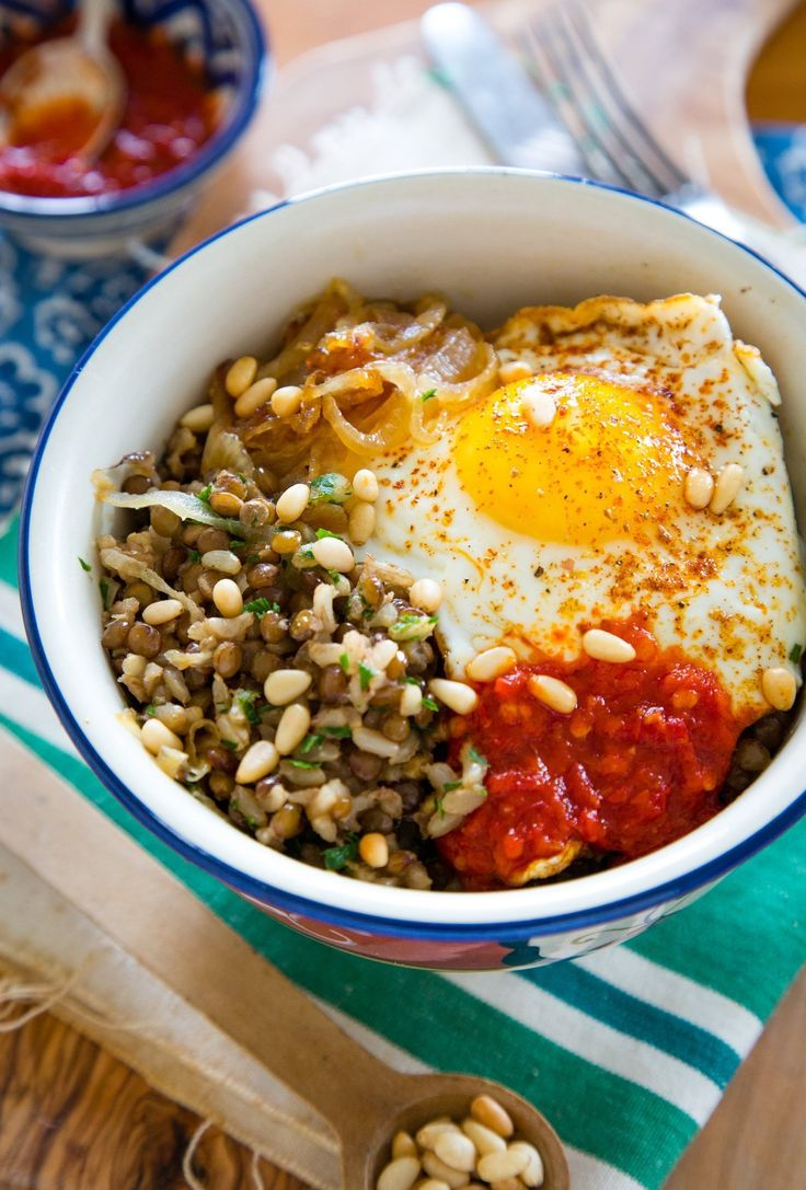 Mujadara — a traditional Middle Eastern recipe made with long-grain rice, brown lentils, and caramelized onions — is typically served as a side dish. For this meatless dinner bowl version, we're serving up these smoky, cumin-scented lentils with a fried egg, spicy harissa, and toasted pine nuts, and calling it dinner!