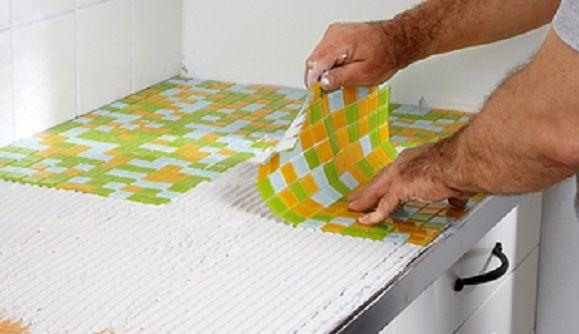 Die Mosaikfliesen legt man in den Kleber ein und richtet die einzelnen Steine gerade aus.