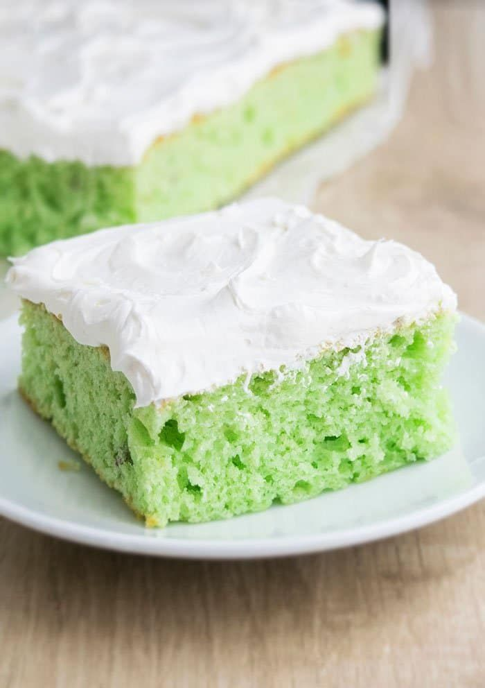 Easy pistachio cake recipe that's soft and moist. It starts off with a yellow cake mix and has pistachio pudding and it's topped off with whipped cream.