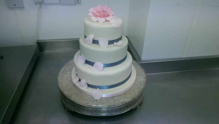 Three tiered wedding cake with cascading petals.