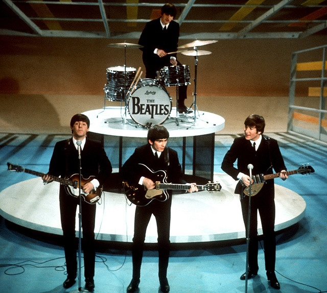 """The Beatles perform on the CBS """"Ed Sullivan Show"""" in New York, in this  Feb. 9, 1964. From left, front, are Paul McCartney, George Harrison and John Lennon. Ringo Starr plays drums in rear."""