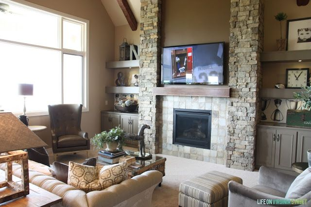 Living room with stone fireplace wall surrounded by gray built-in cabinets and shelving.