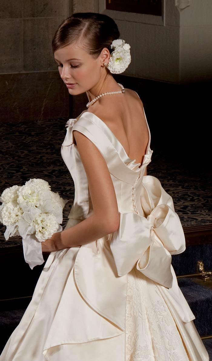 """V字カットとリボンが印象的な後姿を演出してくれるウェディングドレス。上質なイタリア製ミカドシルクを100%使用し、洗練されたクラシカルなデザインが、見る人を圧倒させる王道のウェディングドレス。<span id=""""more-188""""></span>フランス製コードリバーレースを使用したロングトレーンが、バックスタイルを優美に表現。オフショルダーのウェディングドレスは、美しい背中のラインをアピールする。"""