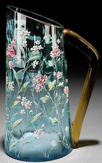 A Moser enameled light blue glass pitcher, of tapered cylindrical form with extensive applied floral, applied amber handle. Czechoslovakia, circa 1876-1925