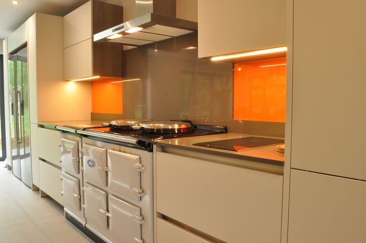 Contemporary Rotpunkt German kitchen with splashes of orange. An electric AGA in Pearl Ash contrasts yet complements the contemporary aesthetic.