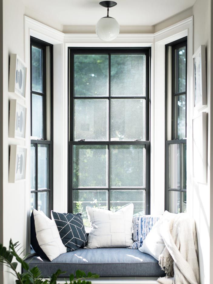 Window seat with throw pillows and black window trim on Thou Swell @thouswellblog